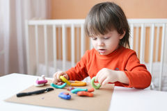 Little boy playing with plasticine. Lovely little boy playing with plasticine at home Stock Photos