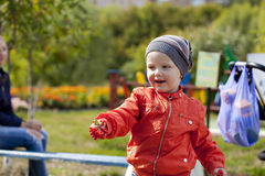 Little boy playing on the playground in the autumn park Royalty Free Stock Photos