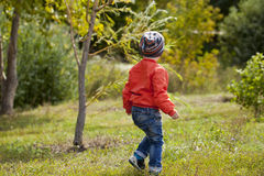 Little boy playing on the playground in the autumn park Stock Image