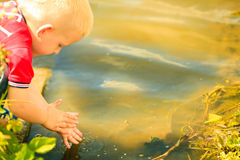 Little boy playing playing with water outdoor washing hands Royalty Free Stock Images