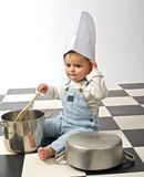 Little boy playing with pots. Little boy druming playing with pots and chef's hat Royalty Free Stock Images