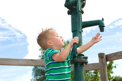 Little boy playing at the Pump Royalty Free Stock Photo