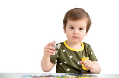 Little boy playing puzzle on a white background Royalty Free Stock Photos