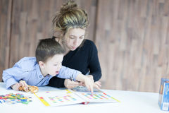 Little boy playing puzzles with his mother Royalty Free Stock Images