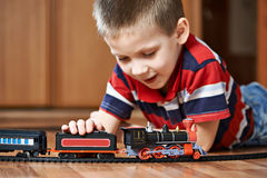 Little boy playing with railway lying on floor Royalty Free Stock Photos