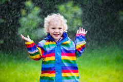 Little boy playing in the rain. Little blond curly boy in a waterproof jacket in rainbow color playing in the rain. Kids having fun outdoors in autumn shower Stock Photo
