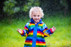 Little boy playing in the rain. Little blond curly boy in a waterproof jacket in rainbow color playing in the rain. Kids having fun outdoors in autumn shower Royalty Free Stock Image