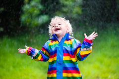 Little boy playing in the rain Royalty Free Stock Image