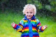 Little boy playing in the rain. Little blond curly boy in a waterproof jacket in rainbow color playing in the rain. Kids having fun outdoors in autumn shower Royalty Free Stock Photography