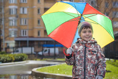 Little boy playing in rainy summer park. Child with colorful rainbow umbrella, waterproof coat and boots jumping in puddle and mud. In the rain. Kid walking in Stock Photo