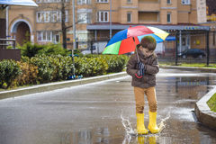 Little boy playing in rainy summer park. Child with colorful rainbow umbrella, waterproof coat and boots jumping in puddle and mud. In the rain. Kid walking in Royalty Free Stock Images