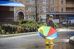 Little boy playing in rainy summer park. Child with colorful rainbow umbrella, waterproof coat and boots jumping in puddle and mud Royalty Free Stock Photo
