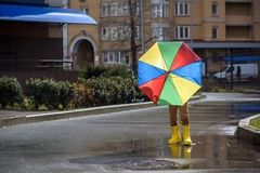 Little boy playing in rainy summer park. Child with colorful rainbow umbrella, waterproof coat and boots jumping in puddle and mud Stock Photos