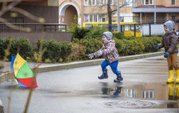 Little boy playing in rainy summer park. Child with colorful rainbow umbrella, waterproof coat and boots jumping in puddle and mud Stock Photo