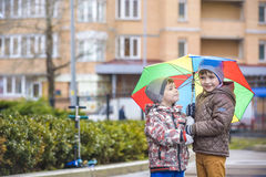 Little boy playing in rainy summer park. Child with colorful rainbow umbrella, waterproof coat and boots jumping in puddle and mud Royalty Free Stock Photos