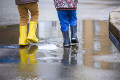 Little boy playing in rainy summer park. Child with colorful rainbow umbrella, waterproof coat and boots jumping in puddle and mud Stock Image