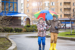 Little boy playing in rainy summer park. Child with colorful rainbow umbrella, waterproof coat and boots jumping in puddle and mud Royalty Free Stock Images