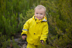 Little boy playing in rainy summer park. Child with colorful rainbow umbrella, waterproof coat and boots jumping in stock photography