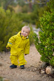 Little boy playing in rainy summer park. Child with colorful rainbow umbrella, waterproof coat and boots jumping in stock images