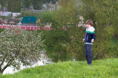 Little boy playing at a river shore in the evening Stock Image