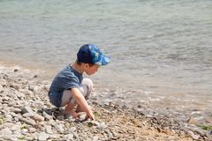 Little boy playing with rocks on the beach. Lake Stock Photos