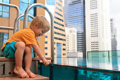 Little boy playing in roof top pool Stock Photo