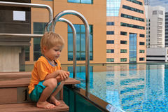 Little boy playing in roof top pool Stock Photos