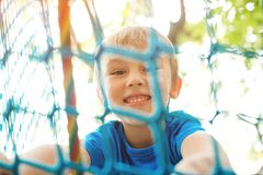 Little boy playing at rope adventure park. Summer holidays concept. Cute child having fun in net tunnel. Modern amusement park for. Kids. Outdoors games stock photos