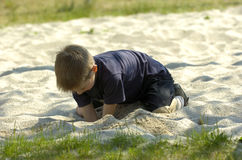 Little boy playing in sand. A cute blond little boy playing digging in the sand in summer on the beach stock image