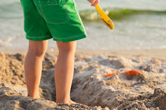 Little boy playing in the sand on the beach Stock Images