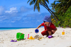 Little boy playing with sand on the beach Royalty Free Stock Images