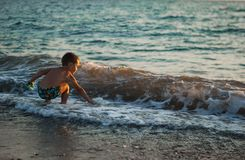 A little boy playing in the sand on the Black Sea in splashes of waves, at sunset of the day. Beach. Golovinka Royalty Free Stock Images
