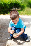Little boy playing in the sand at playground Stock Photo