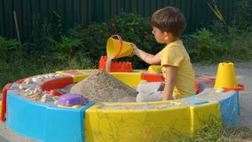Little boy playing with sand in a sandbox. Cute boy playing with sand in a sandbox stock footage