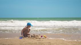 A little boy is playing in the sand on the sea, little legs and fingers, a background of sea yellow sand and blue water stock video footage