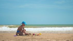 A little boy is playing in the sand on the sea, little legs and fingers, a background of sea yellow sand and blue water stock video