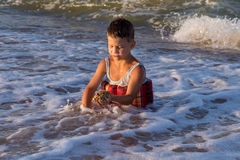 Little boy playing with sand in sea surf Royalty Free Stock Photography