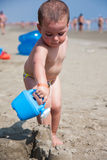 Little boy playing with sand and watering can at sea italy beach Royalty Free Stock Images
