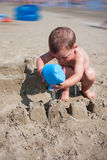 Little boy playing with sand and watering can at sea italy beach Stock Images