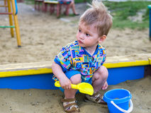 Little boy playing in a sandbox. Little blond boy playing in a sandbox look away from the camera. He is holding a yellow shovel in front of him blue bucket Stock Image