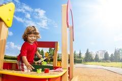 Little boy playing in sandbox Stock Image