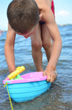 Little boy playing on the sea Stock Images