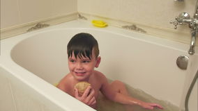 Little boy playing with seashell while taking bath in bathtub. Slow motion shot. Professional shot in 4K resolution. 092. You can use it e.g. in your stock video footage