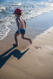 Little boy playing on the seashore Stock Image