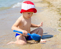 Little boy playing in shallow surf Stock Image