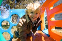 Little Boy Playing on Slide. Cute little boy playing on slide on a fall day Royalty Free Stock Image