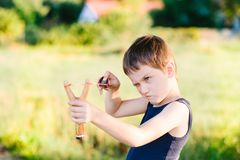 Little boy playing with slingshot Royalty Free Stock Photo