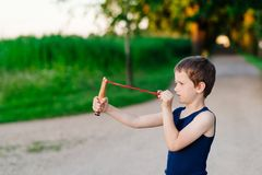 Little boy playing with slingshot Stock Photos