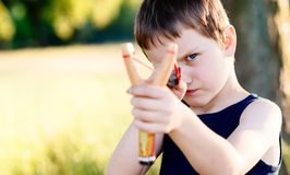 Little boy playing with slingshot Stock Photography