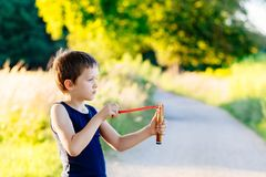 Little boy playing with slingshot Royalty Free Stock Photography